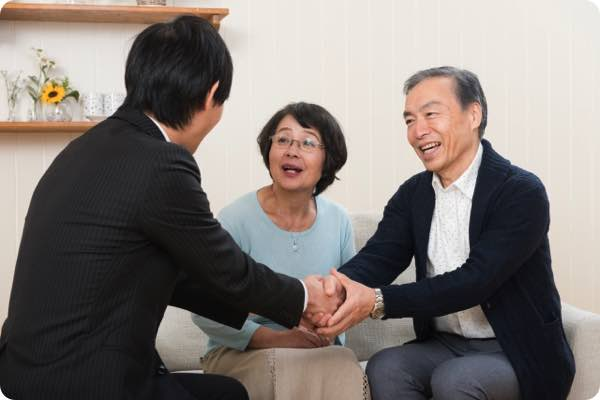 遺品整理会社と握手する老夫婦