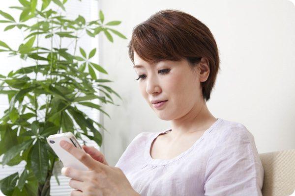 携帯を見つめる女性